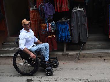 Scott Doolan beraktivitas dengan kursi rodanya di Kathmandu, Nepal, Kamis (15/3). Pria Australia ini bertekad mendaki  hingga basecamp Everest yang berada di ketinggian 5.364 mdpl dengan kursi roda tanpa bantuan. (AFP Photo/Prakash Mathema)
