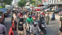 Petugas gabungan melakukan penyekatan PPKM Level 4 di Jalan Raya Margonda, Kota Depok. (Liputan6.com/Dicky Agung Prihanto)