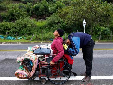 Migran Venezuela, Jefferson Alexis dan ayahnya, Jose Agustin Lopez, duduk di kursi roda, beristirahat ketika melakukan perjalanan yang menghubungkan Cucuta dan Pamplona di Norte de Santander Department, Kolombia, 15 September 2018. (AFP/SCHNEYDER MENDOZA)