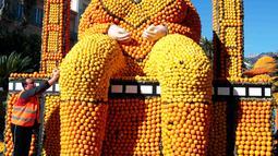 Pekerja merapikan susunan lemon dan jeruk yang menyerupai tubuh wanita di festival lemon, Menton , Prancis (10/2). 140 ton jeruk dan lemon dihabiskan untuk memeriahkan festival ini. (REUTERS/Eric Gaillard)