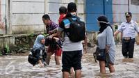 Banjir di kawasan Bukit Duri telah membuat seorang wanita terperosok ke dalam lubang yang tak terlihat karena tertutup oleh genangan air, Jakarta, Selasa (21/2). Tampak seorang lelaki membantu seorang wanita usai terperosok. (Liputan6.com/Yoppy Renato)
