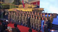 Pemimpin Korea Utara Kim Jong-un (tengah) berpose untuk foto bersama dengan pilot pesawat tempur yang melakukan penerbangan demonstrasi pada pembukaan pameran sistem senjata di Pyongyang, Korea Utara, Senin, Okt .11, 2021. (KCNA/AP)