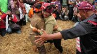 Sejumlah warga menyaksikan aksi dua pegulat tradisional (gulat okol), usai upacara Sedekah Bumi Kelurahan Made kecamatan Sambi Kerep, Surabaya, di Taman Bungkul Surabaya. (Antara)
