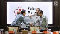 Presdir PT Astra International Tbk Prijono Sugiarto berjabat tangan dengan Ketua Umum PMI Jusuf Kalla pada acara penyerahan bantuan 10 unit truk tangki air di Kantor PMI, Jakarta, Jumat (8/2). (Liputan6.com/Fery Pradolo)