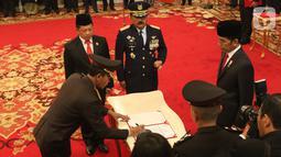 Komjen Pol Idham Azis (kiri) menandatangani berkas disaksikan Presiden Joko Widodo (kanan), Menteri Dalam Negeri Tito Karnavian (kedua kiri), Panglima TNI Hadi Tjahjanto (kedua kanan) saat upacara pelantikannya sebagai Kapolri di Istana Negara, Jakarta, Jumat (1/11/2019). (Liputan6.com/Angga Yuniar)