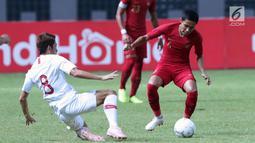 Pemain Timnas Indonesia, Evan Dimas Darmono (kanan) berebut bola dengan pemain Hong Kong pada laga uji coba internasional di Stadion Wibawa Mukti, Cikarang, Selasa (16/10). Babak pertama, Indonesia unggul 1-0. (Liputan6.com/Helmi Fithriansyah)