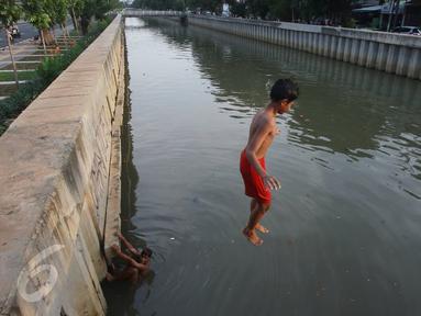 Seorang anak melompat ke anak Kali Ciliwung di Jakarta, Rabu (13/7). Bersihnya kali yang berada di Ibu Kota itu dimanfaatkan anak-anak sekitar untuk berenang sambil mengisi waktu libur sekolah. (Liputan6.com/Immanuel Antonius)