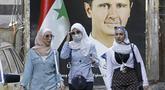 Warga berjalan di depan poster Presiden Bashar al-Assad dekat Masjid Agung Umayyah di Damaskus, Suriah, 23 September 2021. Berbeda dengan kondisi sebagian besar negeri, Ibu Kota Damaskus tidak terlalu menderita akibat perang Suriah yang sudah memasuki tahun ke-10. (LOUAI BESHARA/AFP)