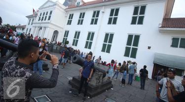 Pengunjung berfoto di depan meriam di kawasan wisata Kota Tua, Jakarta, Senin (12/12). Kota Tua masih menjadi salah satu destinasi wisata bagi warga Jakarta dan sekitarnya untuk menghabiskan waktu liburan. (Liputan6.com/Immanuel Antonius)