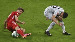 Pemain Bayern Munchen Thomas Mueller (kiri) berebut bola dengan pemain Bayer Leverkusen Exequiel Palacios pada pertandingan Bundesliga di Stadion Allianz Arena, Munchen, Jerman, Selasa (20/4/2021). Bayern Munchen menang 2-0. (Christof Stache, Pool via AP)