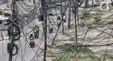 Kendaraan melintas dekat instalasi kabel yang semrawut di Jalan Raya Bekasi, Cakung, Jakarta, Rabu (30/9/2020). Minimnya perawatan pascapembebasan lahan permukiman untuk proyek Tol Dalam Kota membuat jaringan kabel listrik di sepanjang jalan tersebut semrawut. (merdeka.com/Iqbal S. Nugroho)
