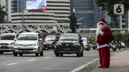 Pria berkostum Sinterklas saat membagikan kopi gratis kepada warga di kawasan Jalan Jenderal Sudirman, Jakarta, Sabtu (19/12/2020). Selain menyambut Natal, pembagian kopi tersebut juga untuk mempromosikan produk unggulan para petani dari berbagai daerah di Indonesia. (Liputan6.com/Johan Tallo)