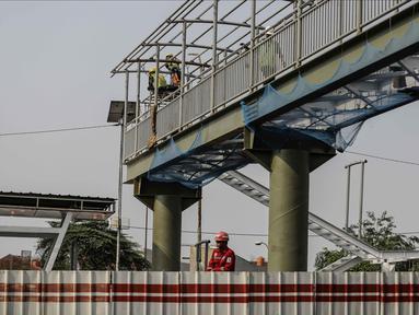 Pekerja menyelesaikan pembangunan halte busway BNN di Kawasan Cawang Jakarta, Jumat (2/3). Pembangunan halte baru tersebut guna menggantikan halte BNN yang lama akibat pembangunan proyek LRT. (Liputan6.com/Faizal Fanani)