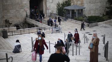 Orang-orang yang mengenakan masker terlihat di luar Kota Tua Yerusalem di tengah pandemi COVID-19 (25/11/2020). (Xinhua/Muammar Awad)