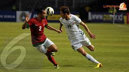 Supardi (Indonesia - 2) tampak berebut bola dengan Dhurgham Ismael Dawood (Irak - 19) dalam kualifikasi Piala Asia 2015 yang digelar di Stadion GBK Jakarta (Liputan6.com/Helmi Fithriansyah)