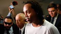 Mantan pemain timnas Brasil, Ronaldinho dikawal oleh polisi meninggalkan kantor pengadilan di Asuncion, ibu kota Paraguay, Jumat (6/3/2020). Ronaldinho bersama saudara laki-lakinya berurusan dengan pihak berwenang Paraguay karena menggunakan paspor palsu untuk memasuki negara itu. (AP/Jorge Saenz)