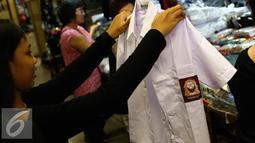 Seorang anak melihat seragam di kawasan Pasar Baru, Jakarta, Selasa (12/7). Menjelang tahun ajaran baru, sejumlah toko penjualan perlengkapan sekolah mulai didatangi warga. (Liputan6.com/Faizal Fanani)