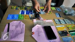 Barang bukti puluhan kartu ATM dari hasil pencurian oleh pelaku yang diamankan Polres Jaksel, Jumat (10/6). Polres Metro Jaksel berhasil meringkus 11 pelaku kejahatan diantaranya perampokan, Begal dan pencurian ATM. (Liputan6.com/Yoppy Renato)