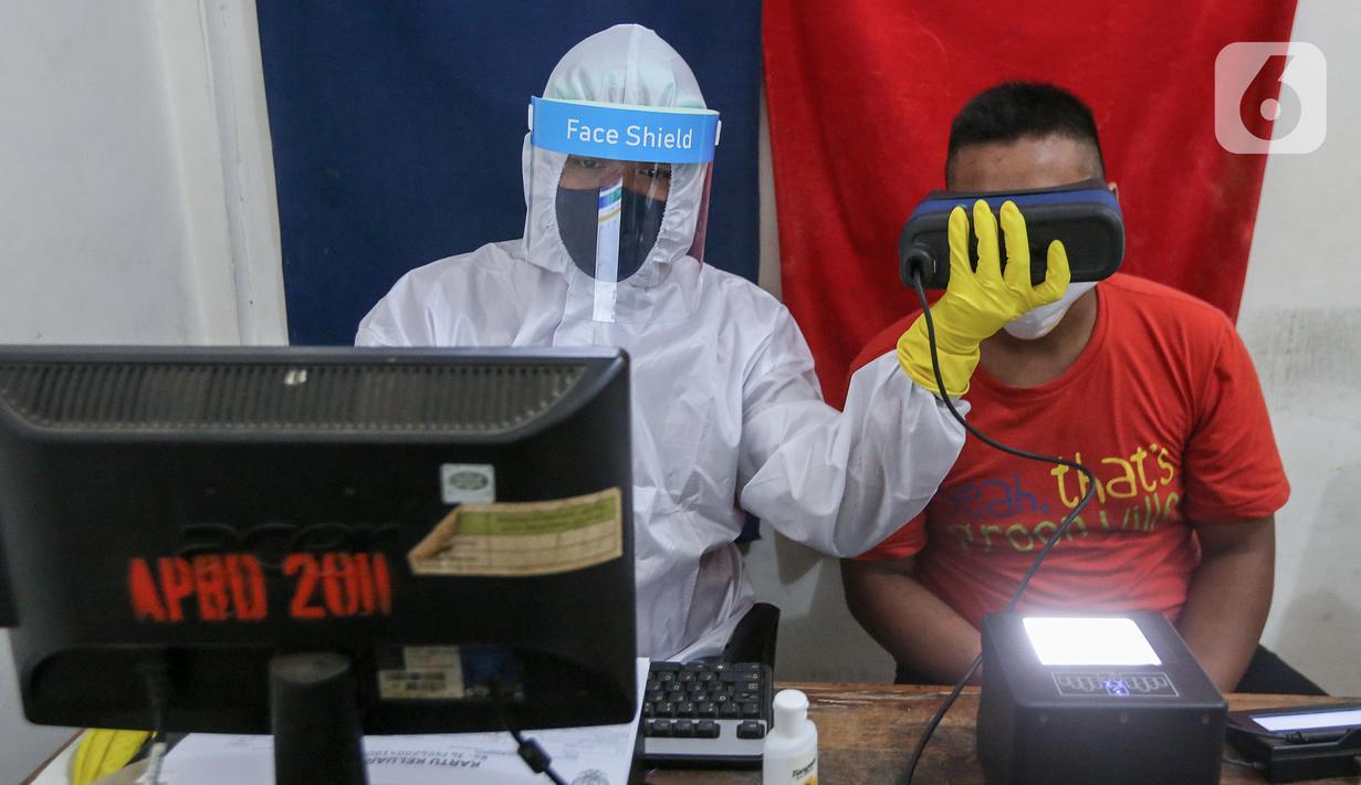 Petugas Dukcapil lengkap dengan APD merekam untuk KTP Elektronik di Kecamatan Pamulang, Tangerang Selatan, Senin (15/6/2020). Dukcapil Tangsel membuka layanan rekaman E-KTP menjelang Pilkada dengan menerapkan ketentuan New Normal guna mencegah penyebaran Virus Covid-19. (Liputan6.com/Fery Pradolo)