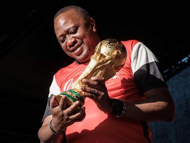 Presiden Kenya Uhuru Kenyatta memegang trofi Piala Dunia FIFA saat Tur Dunia di Gedung Negara, Nairobi (26/2). Trofi ini terbuat dari emas murni 18 karat dengan dasar perunggu, setinggi 36,8 sentimeter dan berat 6,1 kilogram. (AFP Photo/Yasuyoshi Chiba)