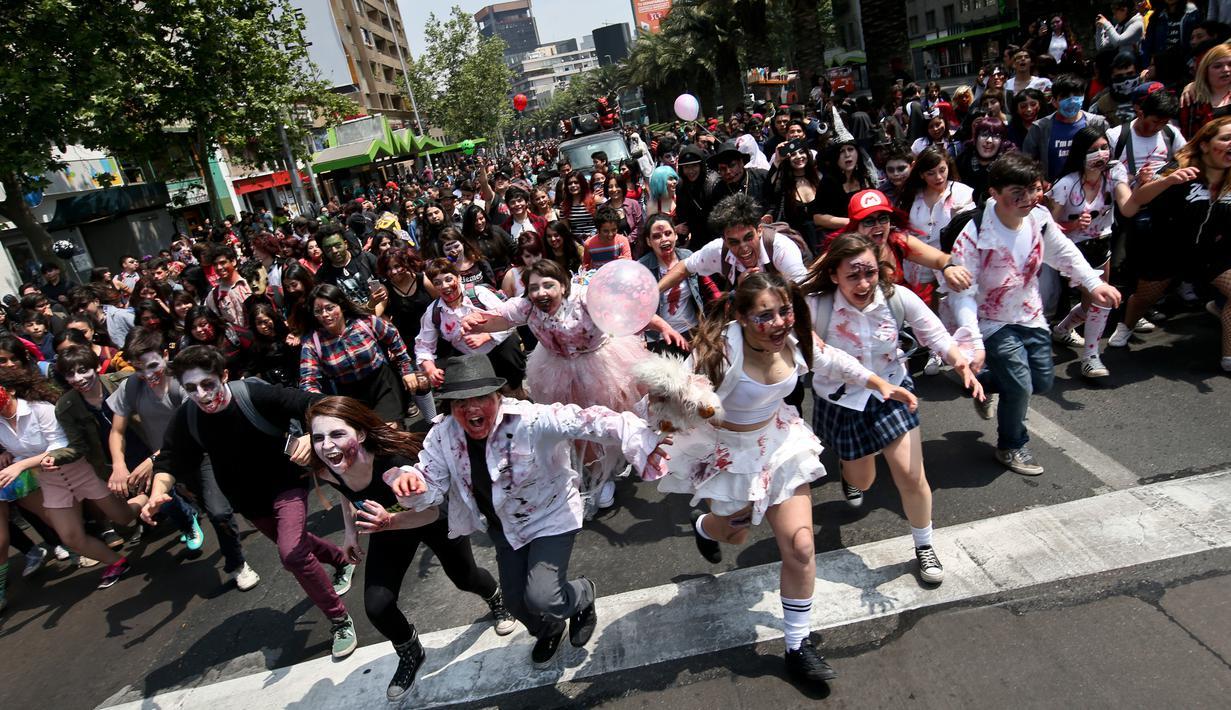 Ratusan orang berkostum menyerupai zombie berpartisipasi dalam perayaan satu dekade Zombie Walk di Santiago, Chile, 13 Oktober 2018. Zombie Walk merupakan acara tahunan yang terinspirasi dari acara televisi AS 'The Walking Dead'. (AP/Esteban Felix)