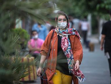 Warga dengan masker melintasi sebuah jalan di pusat Kota Teheran, 28 Juni 2020. Presiden Iran Hassan Rouhani pada Minggu (28/6) mengatakan mengenakan masker di tempat umum akan menjadi wajib mulai pekan depan Di tengah meningkatnya infeksi dan kematian akibat COVID-19. (Xinhua/Ahmad Halabisaz)