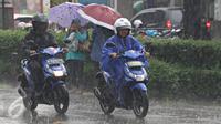 Warga menerobos hujan yang mengguyur kawasan Pondok Labu, Jakarta Selatan, Rabu (2/12). (Liputan6.com/Immanuel Antonius)