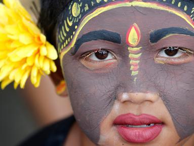 "Seorang pemuda berpartisipasi dalam ritual Hindu ""Grebeg"" di Desa Tegallalang, Bali, Rabu (30/1). Dalam ritual dua tahunan ini, para pemuda berkeliling kampung dengan riasan tubuh warna-warni untuk menangkal Roh jahat. (AP/Firdia Lisnawati)"