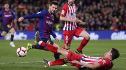 Striker Barcelona, Lionel Messi, berusaha melewati pemain Atletico Madrid, Jose Maria Gimenez, pada laga La Liga di Stadion Camp Nou, Sabtu (6/4). Barcelona menang 2-0 atas Atletico Madrid. (AP/Manu Fernandez)