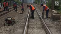 Petugas melakukan perawatan jalur rel kereta api di Buaran Pondok Kopi, Jakarta, Kamis (13/9). Perawatan dilakukan untuk menjamin keselamatan perjalanan kereta dan mencegah terjadi amblesnya bantalan rel. merdeka.com/imam buhori