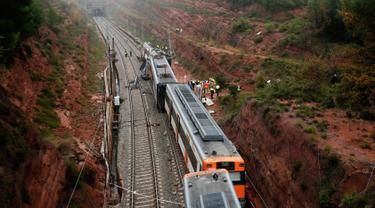 Personel darurat berdiri dekat kereta komuter yang tergelincir dari rel di Vacarisses, Barcelona, Selasa (20/11). Sedikitnya 1 orang tewas akibat longsor yang menerjang sebuah kereta hingga menyebabkannya kereta keluar jalur. (Pau Barrena/AFP)