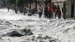 Sejumlah warga berdiri di trotoar melihat salju tebal yang menutupi jalan di wilayah timur Guadalajara, Jalisco, Meksiko (30/6/2019). Pemerintah daerah setempat mengatakan sebanyak 200 rumah rusak dan puluhan kendaraan tersapu di dalam kota dan beberapa distrik di sekitarnya. (AFP Photo/Ulises Ruiz)
