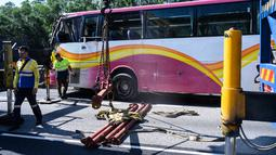 Sejumlah petugas mengevakuasi sebuah bus setelah bertabrakan dengan taksi di Hong Kong (30/11). Lima orang tewas dan 32 luka-luka setelah akibat kecelakaan tersebut. (AFP Photo/Anthony Wallace)