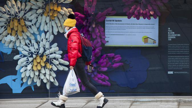 Seorang wanita yang mengenakan masker berjalan melewati Bata Shoe Museum yang tutup di Toronto, Kanada, 23 November 2020. Kanada telah mengonfirmasi total 337.555 kasus COVID-19 dan 11.521 kematian. (Xinhua/Zou Zheng)