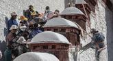 Para pekerja mengecat tembok Istana Potala dalam rangka renovasi tahunan kompleks arsitektur kuno tersebut di Lhasa, ibu kota Daerah Otonom Tibet, China barat daya, pada 28 Oktober 2020. (Xinhua/Sun Fei)