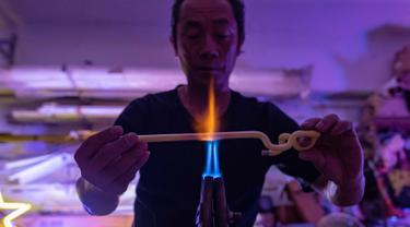Wu Chi-kai mendemonstrasikan bagaimana membuat neon sign selama wawancara dengan AFP di Hong Kong (16/4). Wu Chi-kai merupakan salah satu pengrajin neon sign yang tersisa dari jenisnya di Hong Kong. (AFP Photo/Philip Fong)