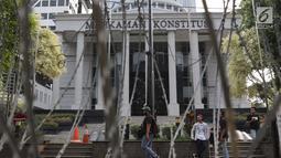 Pewarta berjalan melintasi halaman depan Gedung Mahkamah Konstitusi, Jakarta, Kamis (13/6/2019). Mahkamah Konstitusi akan menggelar sidang Perselisihan Hasil Pemilihan Presiden/Wakil Presiden Pemilu 2019 pada, Jumat (14/6). (Liputan6.com/Helmi Fithriansyah)