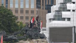 Massa aksi demo tolak omnibus law UU Cipta Kerja naik ke atas patung arjuna wiwaha membawa bendera merah putih di Jalan Medan Merdeka Barat, Jakarta Pusat, Selasa (20/10/2020). Mereka sempat mengibarkan bendera selama kurang lebih lima menit di atas patung. (Liputan6.com/Herman Zakharia)