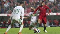 Striker Portugal, Cristiano Ronaldo, berusaha melewati pemain Aljazair pada laga uji coba di Estadio da Luz, Jumat (8/6/2018). Portugal menang 3-0 atas Aljazair. (AP/Armando Franca)