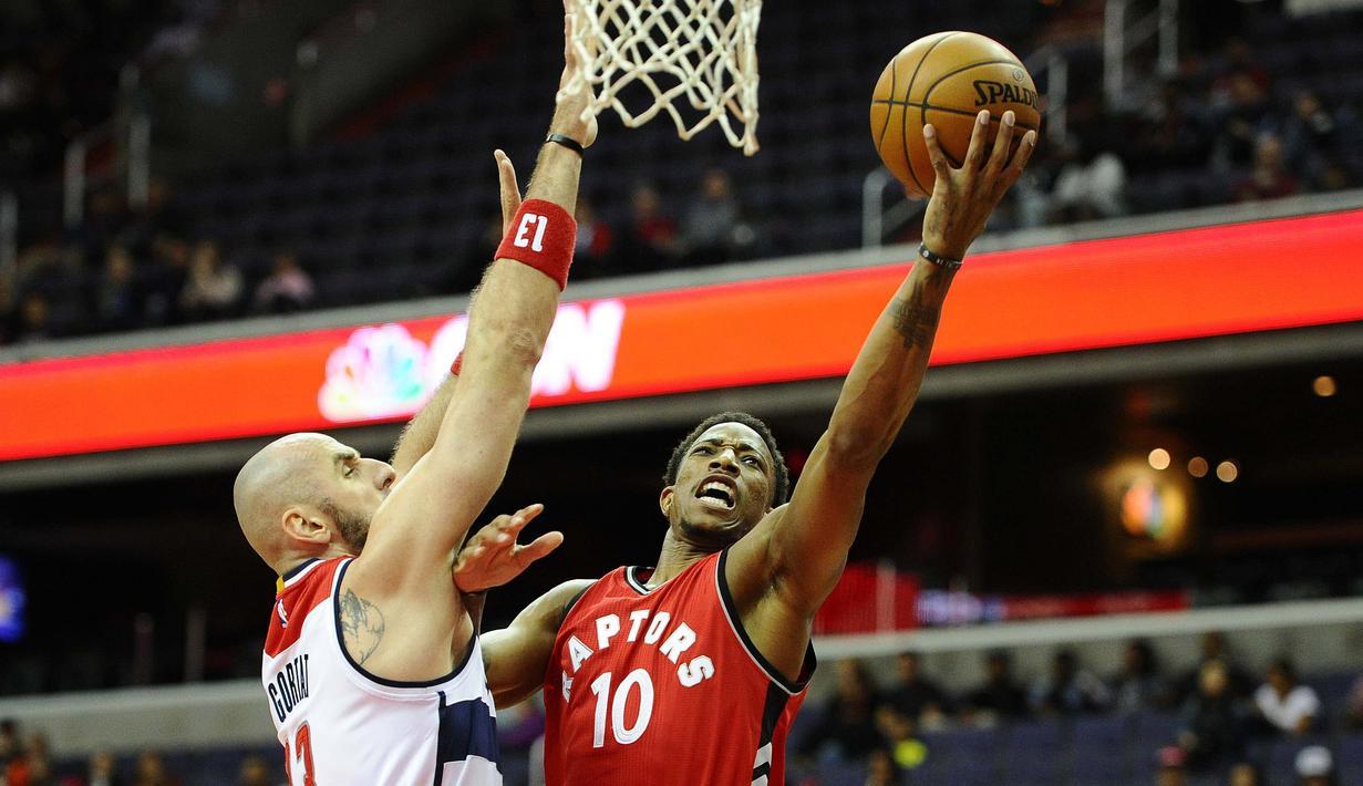 Pemain Toronto Raptors, DeMar DeRozan #10 mencoba melakukan saat dihadangan pemain Washington Wizards, Marcin Gortat #13 pada laga NBA Preseason di Verizon Center, Ssabtu (22/10/2016) WIB. (Mandatory Credit: Brad Mills-USA TODAY Sports)