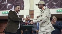 Jenderal Mohammed Hamdan Dagalo, kanan, dan pemimpin gerakan pro-demokrasi Sudan Ahmad al-Rabiah berjabat tangan setelah menandatangani dokumen pembagian kekuasaan di Khartoum, Sudan, Rabu, 17 Juli 2019. (AP/Mahmoud Hjaj)