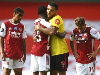 Pemain Arsenal, Ainsley Maitland-Niles, berusaha menenangkan pemain Watford, Troy Deeney, pada laga Premier League di Stadion Emirates, Minggu (26/7/2020). Arsenal menang 3-2 atas Watford. (AP photo/Neil Hall, Pool)