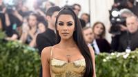 Aktris Kim Kardashian berpose saat menghadiri Met Gala 2018 di Metropolitan Museum of Art, New York (7/5). Kim Kardashian tampil seksi mengenakan gaun emas super ketat. (AP Photo/Evan Agostini)