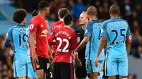 Para pemain Manchester City dan Manchester United melakukan protes kepada wasit Martin Atkinson pada laga Premier League di Stadion Etihad, Manchester, Kamis (27/4/2017). (AFP / Paul Ellis)