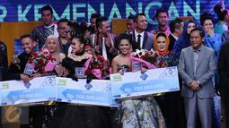 Weni (tengah) memamerkan hadiah yang didapat usai dinobatkan menjadi juara D'Academy Asia 2 di Studio 5 Indosiar, Jakarta, Kamis (29/12). Weni berhasil unggul atas dua finalis lainnya, Rani dan Irsya ditempat ketiga. (Liputan6.com/Helmi Fithriansyah)