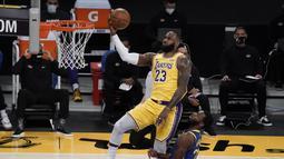 Pebasket LA Lakers LeBron James (kiri) berupaya memasukkan bola dalam pertandingan NBA melawan Golden State Warriors di Staples Center,  Los Angeles, California, Amerika Serikat, Senin (18/1/2020). (AP Photo/Jae C. Hong)
