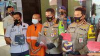 Polisi mengapit tersangka pembunuhan teman kerja di Kota Malang gara - gara sakit hati saat bermain game online (Liputan6.com/Zainul Arifin)