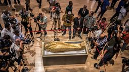 Para jurnalis mengambil gambar peti mati emas mumi Nedjemankh yang dipajang di Museum Nasional Peradaban Mesir, Kairo, Selasa (1/10/2019). Peti mati itu dikembalikan ke Mesir dari AS pekan lalu setelah ditetapkan sebagai barang antik yang dijarah. (Khaled DESOUKI/AFP)