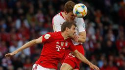 Striker Bayern Munchen, Thomas Mueller, duel udara dengan bek RB Leipzig, Marcel Halstenberg, pada laga DFB Pokal di Stadion Olympic, Berlin, Sabtu (25/5). Munchen menang 3-0 atas Leipzig. (AFP/Odd Andersen)