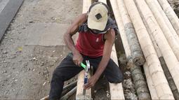 Penjual sedang mengerjakan pohon pinang yang akan dijual di kawasan Tanjung Barat, Jakarta, Kamis (8/8). Penjualan pohon Pinang untuk perlombaan panjat pinang memeriahkan peringatan HUT Kemerdekaan RI tersebut mulai marak. (Liputan6.com/Herman Zakharia)